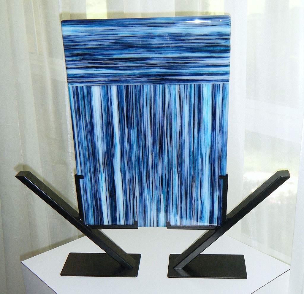 "Blue Rivers (glass - 10"" x 14""; total – 18"" x 17.5""), $250 This piece utilizes an ""on-edge"" fusing process. Flat sheets of glass are cut into strips and stood on their edge in the kiln. The glass is damned to control the glass flow and insure the face of the glass fuses together. After fusing, the edges are cold-worked with a wet-belt sander. Finally, the glass is placed back in the kiln to be fire-polished."